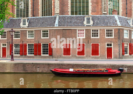 Red boat on canal and typical brick dutch house on background in Amsterdam, Netherlands. - Stock Photo