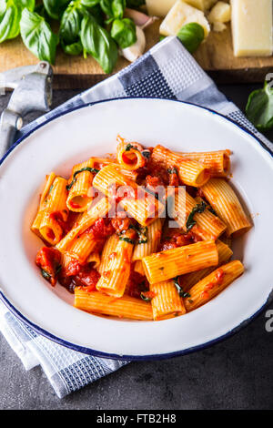 Pasta. Italian and Mediterranean cuisine. Pasta Rigatoni with tomato sauce basil leaves garlic and parmesan cheese. - Stock Photo