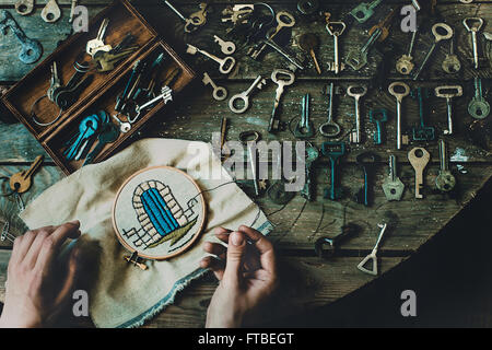 Wes Anderson from above top view hands keys embroidery needlework locked princess in the tower needle open texture - Stock Photo