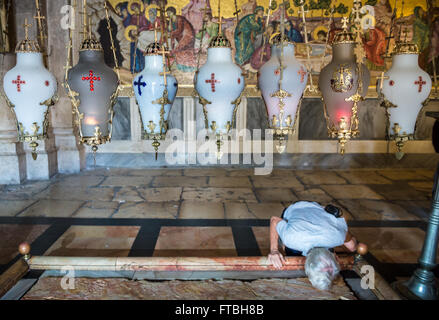 Lamps over Stone of Anointing in Church of Holy Sepulchre, Jerusalem, Israel and mosaic depicts anointing of Jesus - Stock Photo