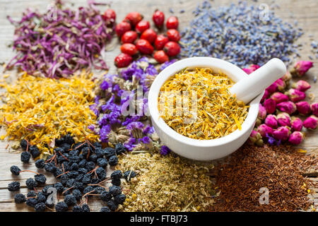 Mortar of dry marigold flowers, herbal tea assortment and berries on table. Herbal medicine. - Stock Photo