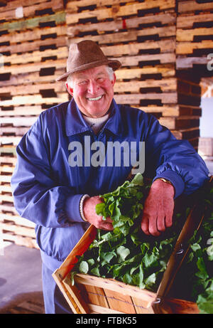 Portrait of smiling male farmer with fresh produce in barn - Stock Photo