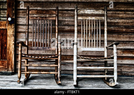 Two old wooden rocking chairs on front porch, part of door and the house's wooden shingles can be seen. Rustic koreshan - Stock Photo