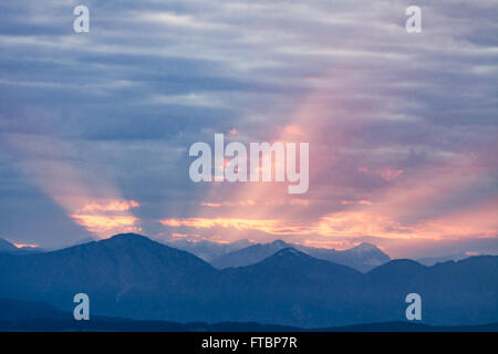 First rays of the rising sun on dawning cloudy sky over dark blue morning Alps mountains - Stock Photo