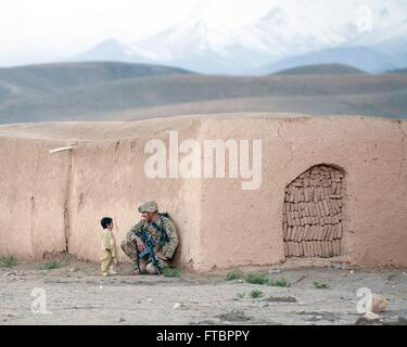 Sgt. Joshua Smith, a paratrooper with the 82nd Airborne Division chats with an Afghan boy during a clearing operation - Stock Photo
