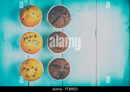 Retro Homemade Chocolate Chip Muffins On Blue Table - Stock Photo