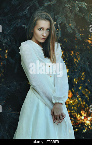 Beautiful woman posing among branches of pine tree  . Winter portrait - Stock Photo
