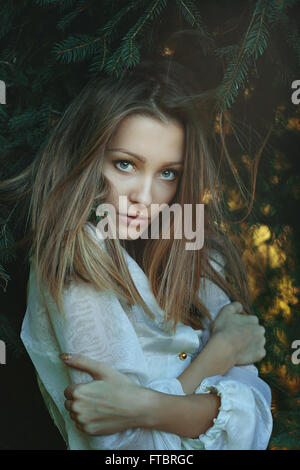 Winter portrait among pine branches of beautiful woman . Seasonal - Stock Photo