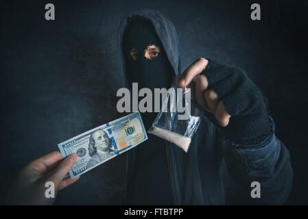 Drug dealer offering narcotic substance to addict on the street, unrecognizable hooded criminal selling drugs in - Stock Photo