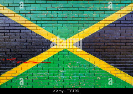 Jamaica flag painted on brick wall in urban environment - Stock Photo