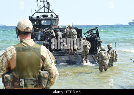 150613-N-HX127-364  Ravlunda, Sweden (June 13, 2015) -- A Royal Marine Beach Master observes US Army Soldiers, Royal - Stock Photo