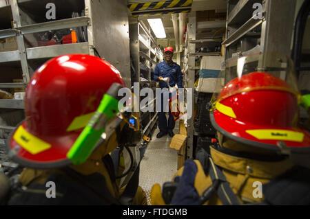 131008-N-NU634-065: MEDITERRANEAN SEA (Oct. 8, 2013) – Damage Controlman 1st class Brandon Young, center, simulates - Stock Photo