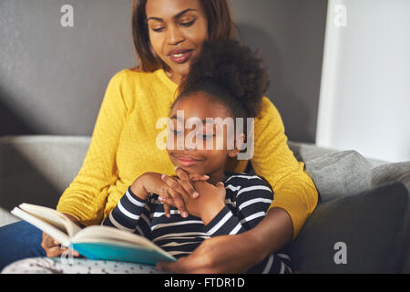 Black mom and daughter reading a book sitting on sofa smiling - Stock Photo