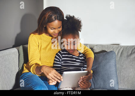 Mom and daughter with tablet sitting in sofa concentrated on learning - Stock Photo