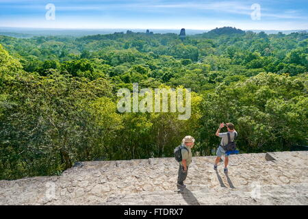 Tourists on the top of Temple IV, Ancient Maya Ruins, Tikal National Park, Yucatan, Guatemala - Stock Photo