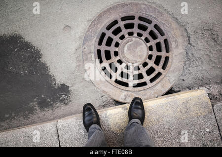 Urbanite man in black new shining leather shoes standing on the roadside near rusty sewer manhole - Stock Photo