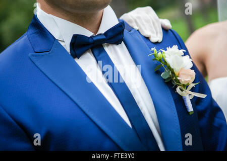 The groom in a blue suit with a bow tie and buttonhole on the lapel of his jacket. - Stock Photo