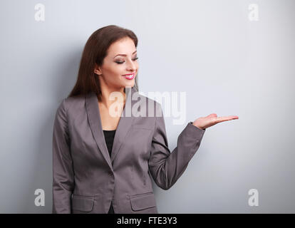 Happy business woman holding something empty in hand and demonstration on blue background - Stock Photo