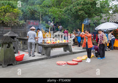 Young Chinese woman praying with burning incense sticks in her hand in front of a shrine. Haikou, Hainan, China. - Stock Photo