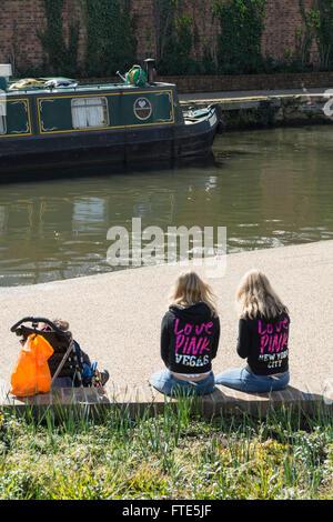 Two 'Love Pink' twin sisters sitting alongside Regent's Canal in London's King's Cross Granary Square Development - Stock Photo