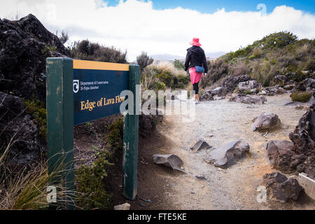 A woman walking past a sign showing the edge of lava flows from Mt Ruapehu in the Tongariro National Park - Stock Photo