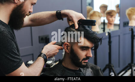 Male barber combing and shaving hair of a male client - Stock Photo