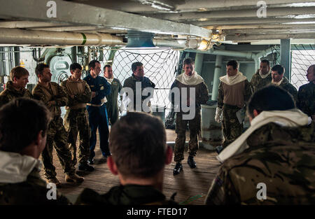 NORTH SEA (Apr. 1, 2014) U.S. Navy Sailors and Royal Marine officers attend a brief aboard the Royal Navy aircraft carrier HMS Illustrious (R06) during exercise Joint Warrior 14-1.  Joint Warrior 14-1, a semi-annual, United Kingdom led training exercise designed to provide NATO and allied forces a unique multi-warfare environment in which to prepare for global operations. The Joint Warrior exercise is intended to improve interoperability between allied navies in an operational challenging environment. Stock Photo