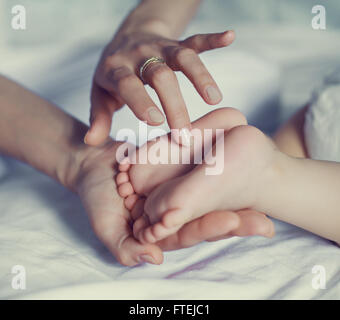 baby's feet in his mother's hands, in bed at home - Stock Photo