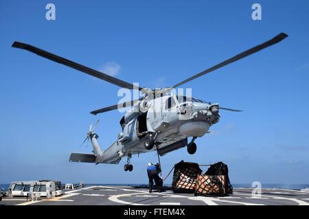 HORN OF AFRICA (Feb. 23, 2015) Flight deck crew members aboard USS Oscar Austin (DDG 79) attach supplies to an SH - Stock Photo