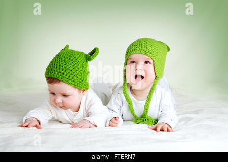 two cute babies lying in frog hats on spft blanket - Stock Photo