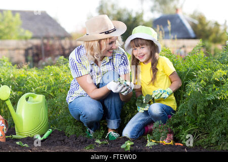 Kid girl with mom happily picking strawberries at strawberry patch - Stock Photo