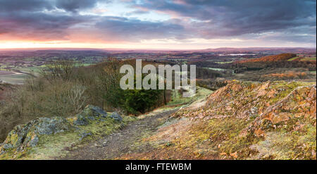 Sunrise lights up the footpath and rocks over Raggedstone Hill on the Malvern Hills, Herefordshire on a cold frosty - Stock Photo