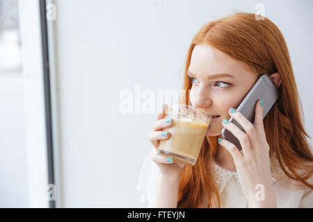 Smiling beautiful young woman drinking coffee and talking on cell phone near the window - Stock Photo