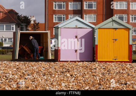 Brighton, UK. 28th Mar, 2016. A woman inspects damage to a beach hut in Hove after winds and rain brought by Storm - Stock Photo