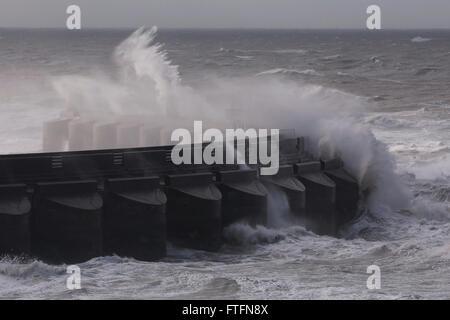 Brighton, UK. 28th Mar, 2016. Waves crash over the Brighton Marina wall as Storm Katie batters the coast at Brighton, - Stock Photo