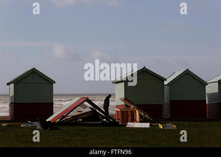 Brighton, UK. 28th Mar, 2016. A passer-by looks at damaged beach huts in Hove after winds and rain brought by Storm - Stock Photo