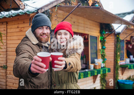 Happy young couple hugging and offering hot drinks to you standing on traditional christmas market - Stock Photo