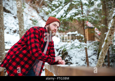 Pensive bearded young man in red hat and checkered shirt standing in winter forest - Stock Photo