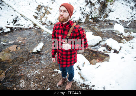 Top view of pensive bearded young man in checkered shirt and hat standing near mountain river in winter - Stock Photo