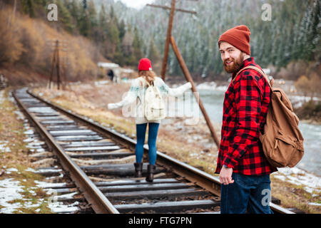 Happy young man and woman with backpacks walking on old railroad in mountains - Stock Photo