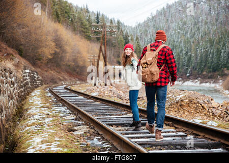 Beautiful couple walking on railroad in mountains together - Stock Photo