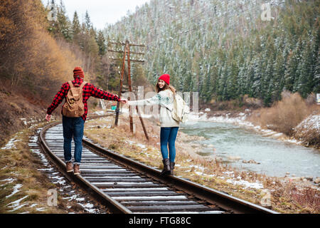 Young couple walking together on old railroad in mountains - Stock Photo