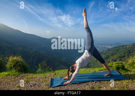 Young sporty fit woman doing yoga oudoors - Stock Photo