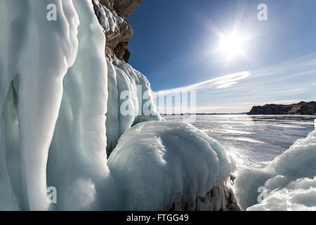 Big icicles on the rock against sunny sky - Stock Photo