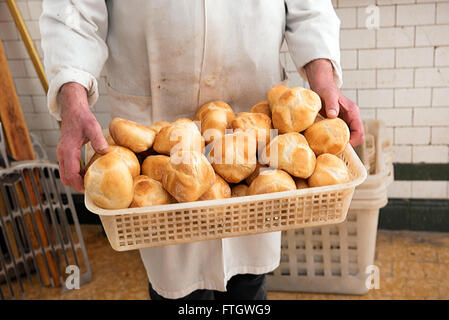 Baker holding a basket full of freshly baked crusty white bread rolls in his white coat at the bakery - Stock Photo