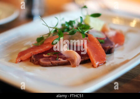 Close up view of seared tuna and salmon, in an english restaurant setting. - Stock Photo