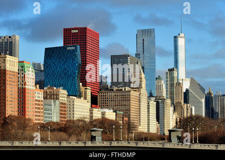 A portion of the Chicago skyline is illuminated beneath some low hanging clouds rising beyond Grant Park in downtown - Stock Photo