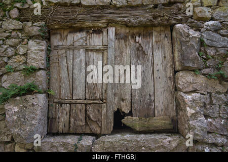 Old door shutters on old stone barn - Stock Photo