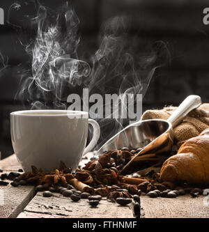 Hot coffee and croissant on old wooden table - Stock Photo