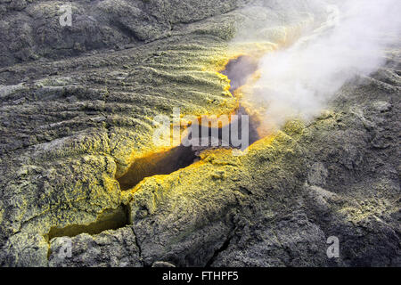 Sulfur vapor escapes from a fumarole which forms yellow-colored crystals around the margins of the crack inside - Stock Photo